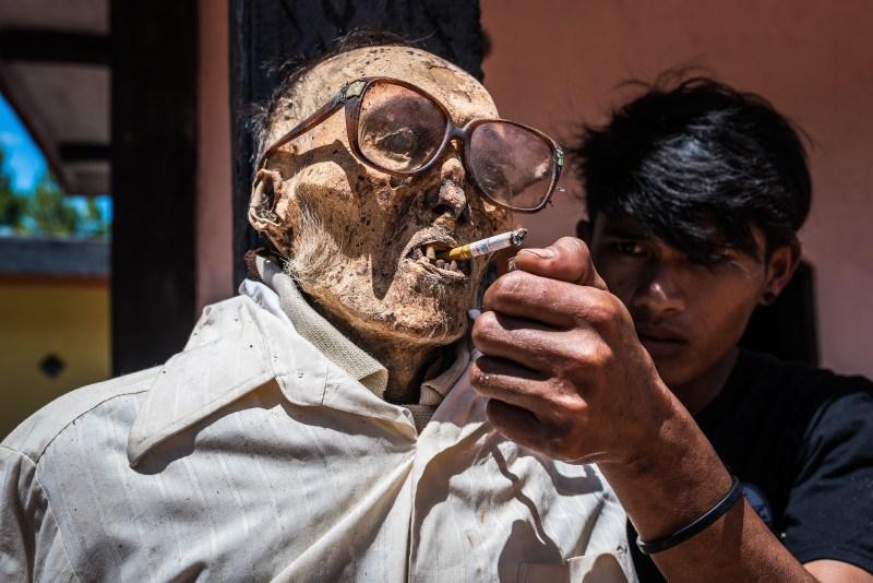 Un membre de la tribu allume la cigarette d'un parent décédé
