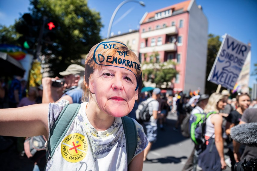 "A woman wears an Angela Merkel mask with the inscription ""Bye bye democracy"" at the demonstration"