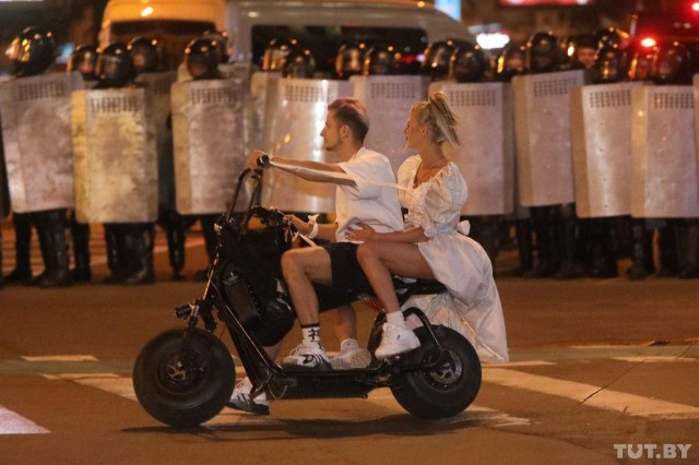 A couple ride a motorcycle through the chaotic protests