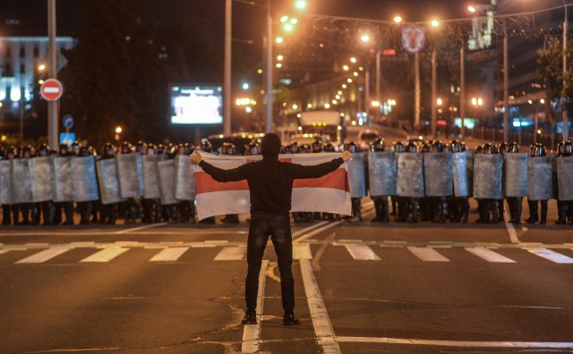 Riot police armed with shield face off against a defiant protester