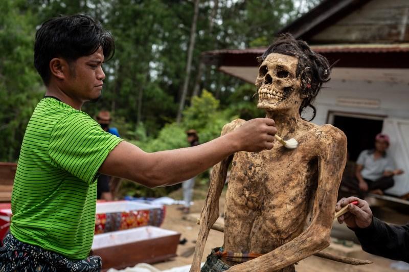 Un cadavre est dépoussiéré par un membre de la tribu
