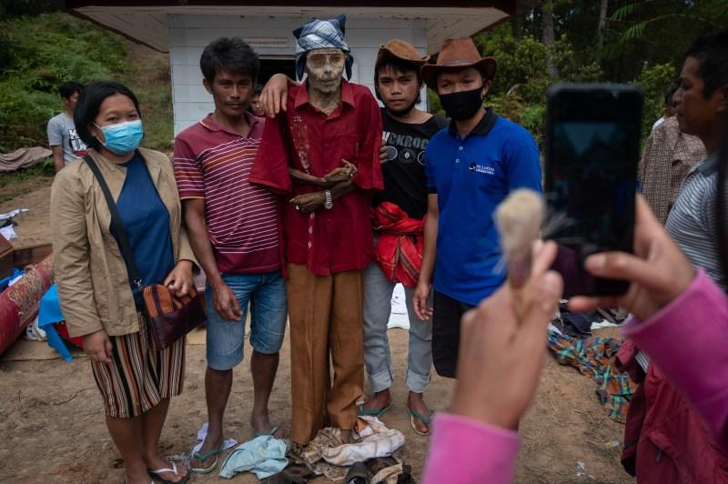 Une famille pose pour une photo avec un parent décédé dans le cadre du rituel