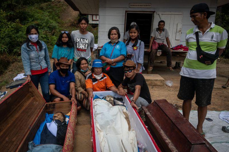 Une famille pose avec les morts dans le cadre du rituel «Mannena»