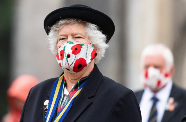 A member of the Royal British Legion wears a face mask emblazoned with poppies outside Winchester Cathedral