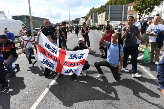 Men wave the England flag as they protest against migrants coming to the country
