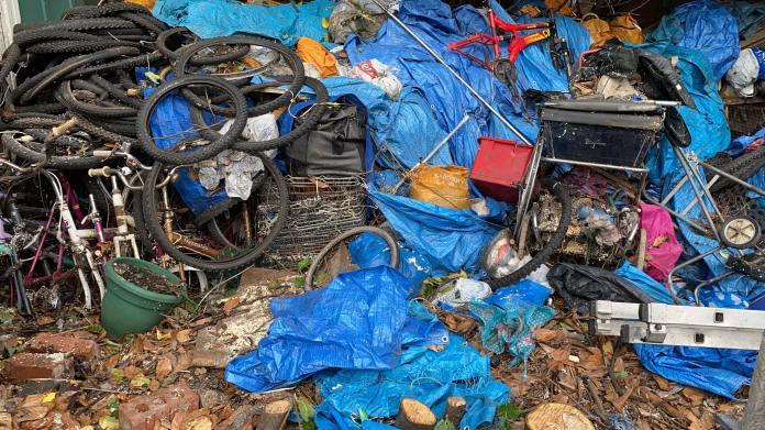 A pile of tires, broken toys and plastic bags lie in the garden next door