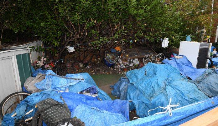 Garbage is draped in tarp, occupying the entire garden next door