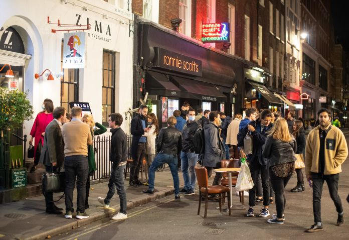 People leave bars and restaurants at closing time in Soho, London