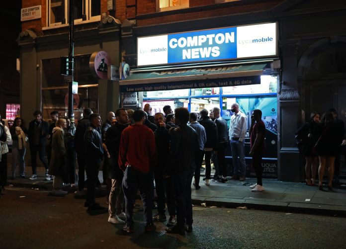 Huge crowds in front of an off-license in London
