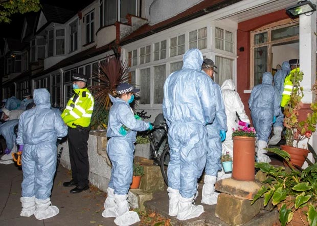 Cops in full forensics suits prepare to the enter a house in London during the investigation