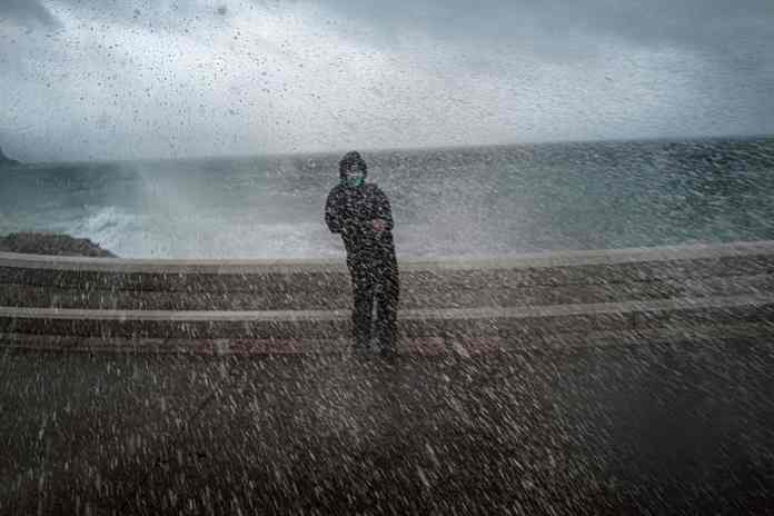 A man is hit by waves on the shore near the Promenade des Anglais in Nice during last night's storm