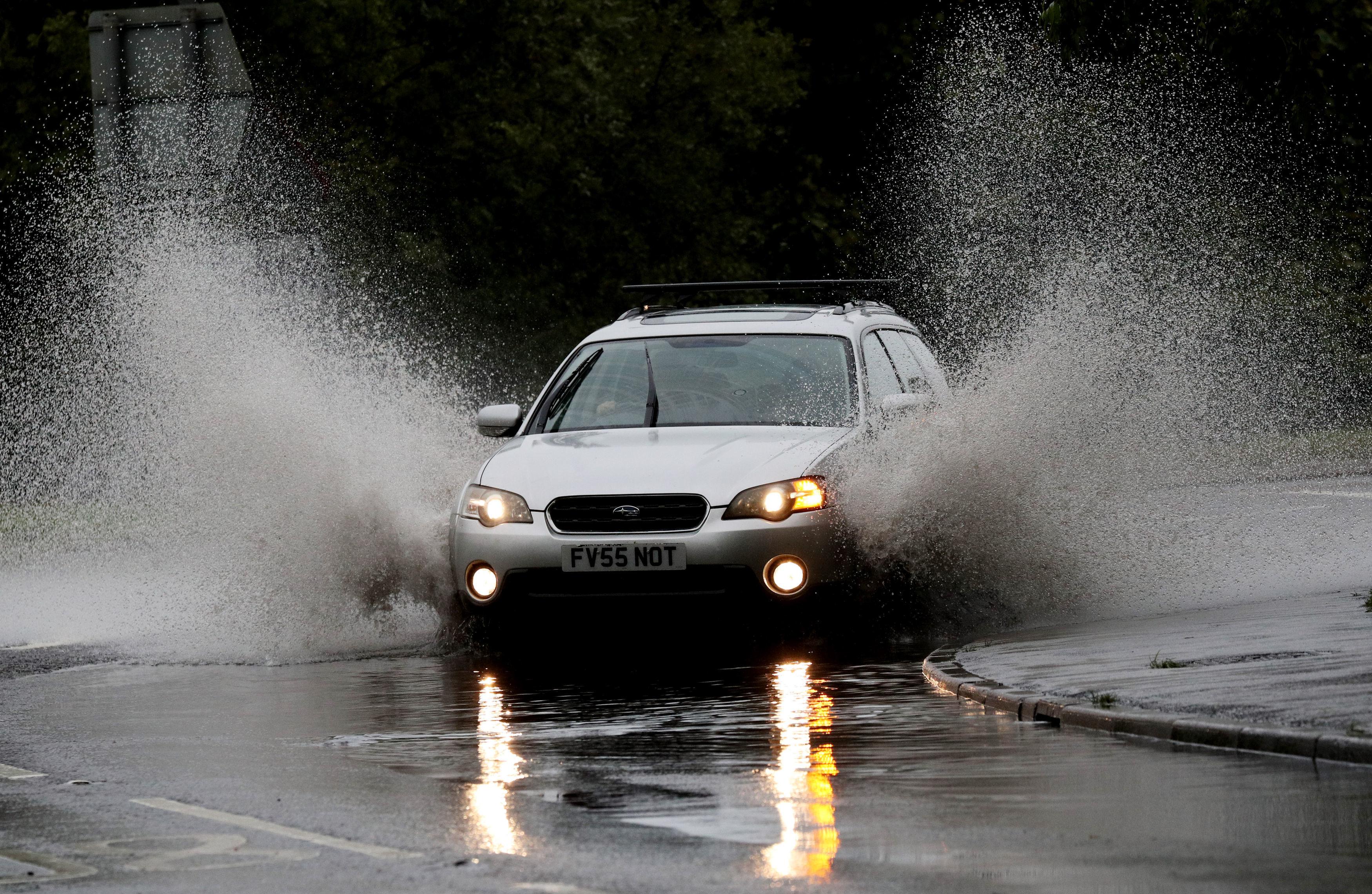ยานพาหนะสร้างสเปรย์เมื่อผ่านน้ำฝนที่สะสมบนวงเวียนใน Maidenhead, Berkshire เมื่อวานนี้