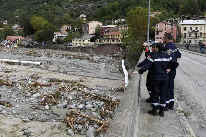 People stand at the side of a damaged road as they gaze into the Roquebilliere valley