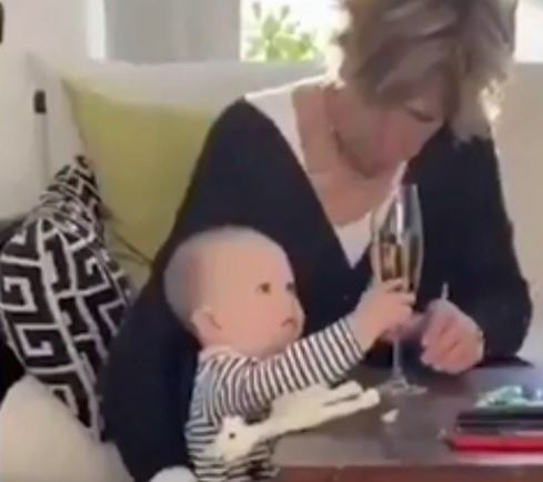 A clip has gone viral showing a woman saving a glass of fizz over a baby
