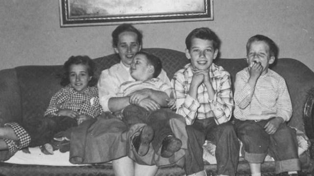 Joe, smiling broadly for the camera, with his three siblings and mum