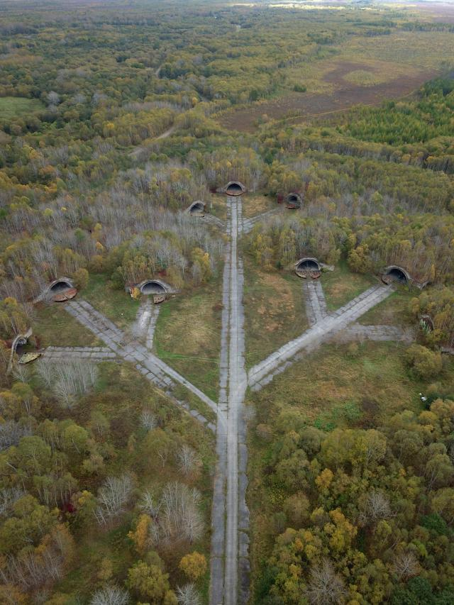 An aerial shot shows the numerous abandoned hangars leading to a central runway