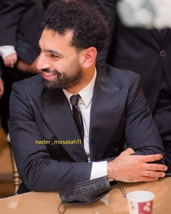Salah was snapped sitting at a table without a mask