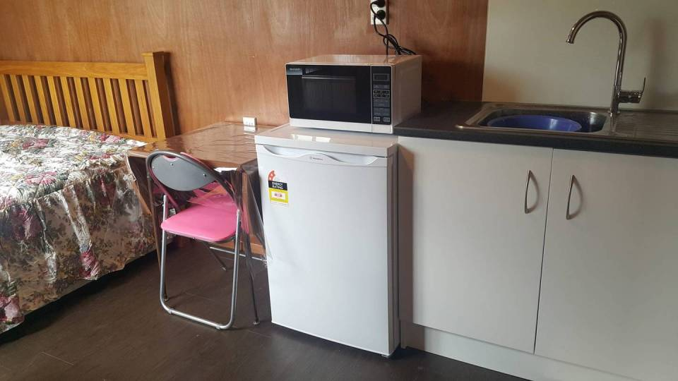 The dingy home has all the mod cons, including a fridge and microwave