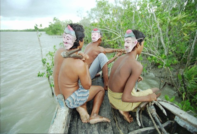 Boys wearing masks on the back of their heads to stop tigersattacking from behind at Sunderbans Tiger Reserve