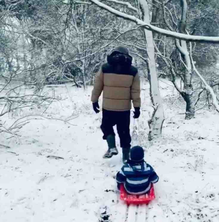 Peter Andre dragging Theo on a sledge