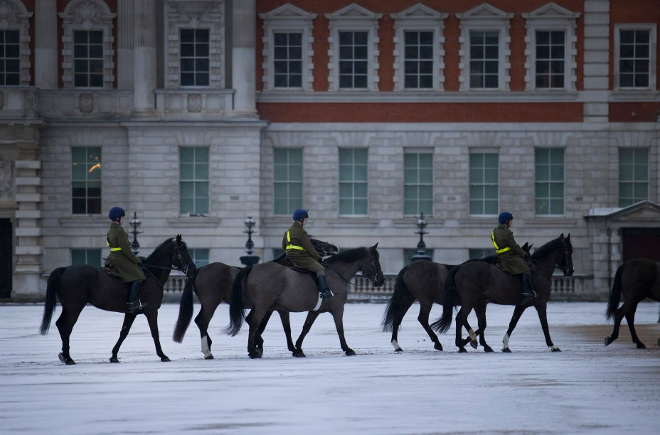 Members of The Blues and Royals exercise their horses on a snowy Horse Guards parade in central London just before dawn