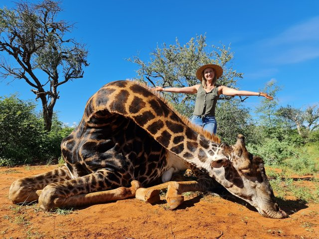 A trophy hunter infuriated animal rights campaigners for posing with the giraffe she shot