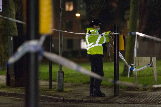 Officers guard the area as a crime scene remains in place