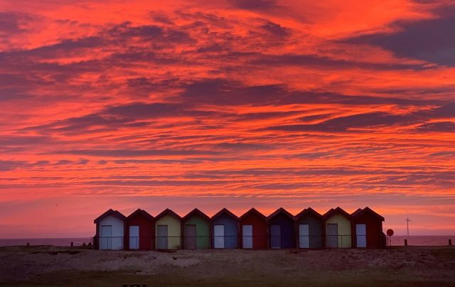 Beach huts stand in front of the stunning red sky at sunrise in Blyth, Northumberland
