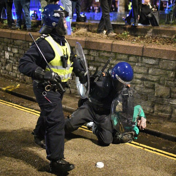 A riot cop holds down a demonstrator during a 'Kill the Bill' protest