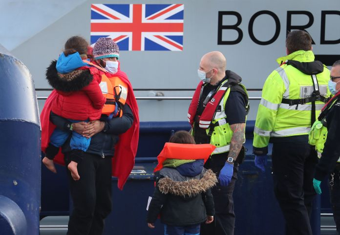 An immigrant carries a young girl as they are brought ashore in Dover, Kent, by Border Force officers