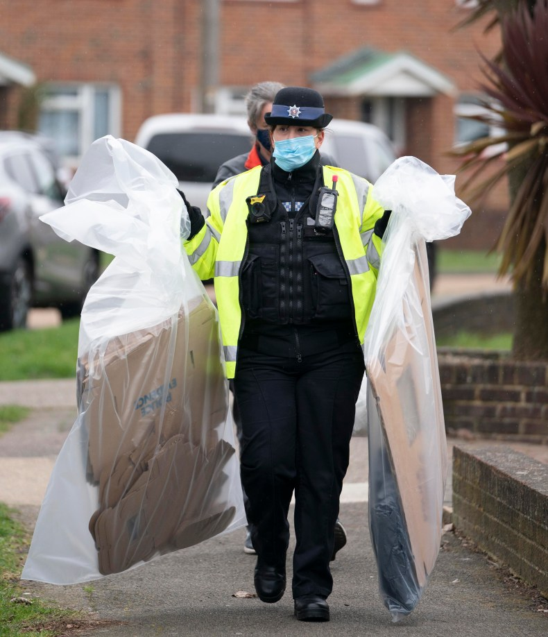 A police officer is seen carrying bags of evidence