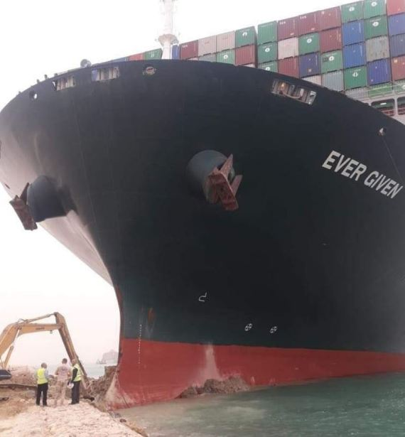The ship's bow is lodged onto one side of the canal
