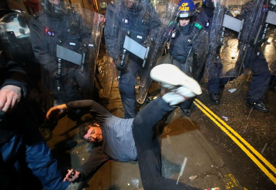 A demonstrator falls during a clash with police officers at a protest against a newly proposed policing bill
