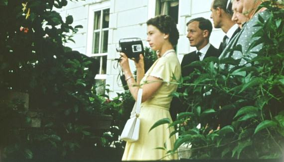 The Queen holds a camera while on tour in New Zealand