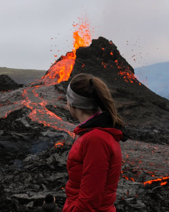 A woman poses near the volcano