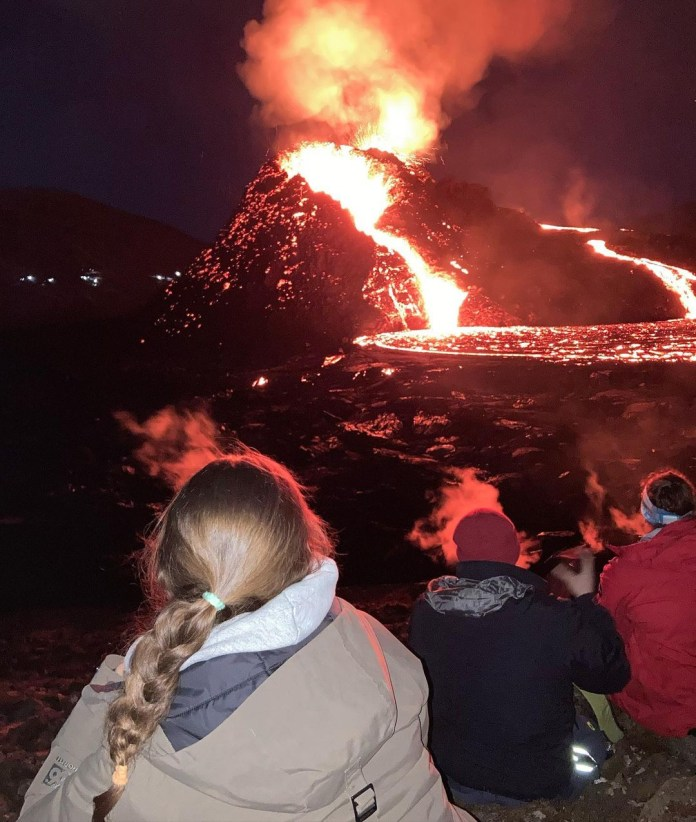 Tourists take photos of the volcano
