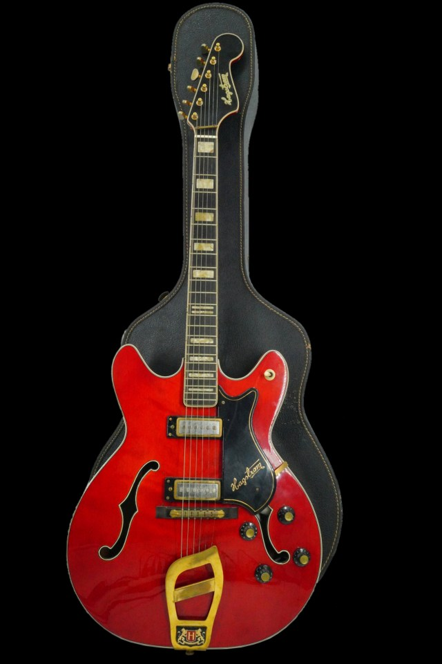 The guitar is cherry or lipstick red with a mother of pearl inlay