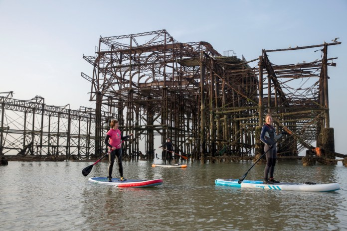 Paddle boarders near the old West Pier in Brighton just after sunrise