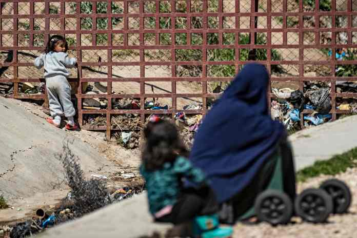A woman sits with her child on the ground at Camp Roj (file image)