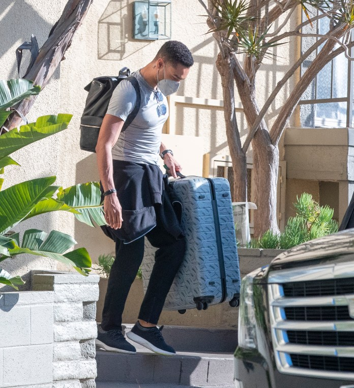 He lifted his suitcase into a waiting chauffeured car in North Hollywood