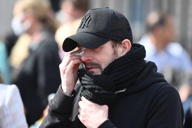 A mourner dabs away a tear