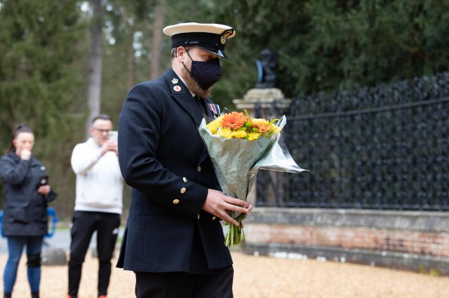 A man laying flowers at Sandringham