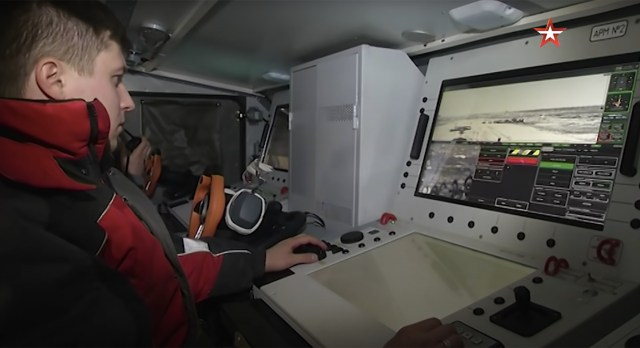 The crew of Uran-9 sit at the controlsinside an armoured vehicle