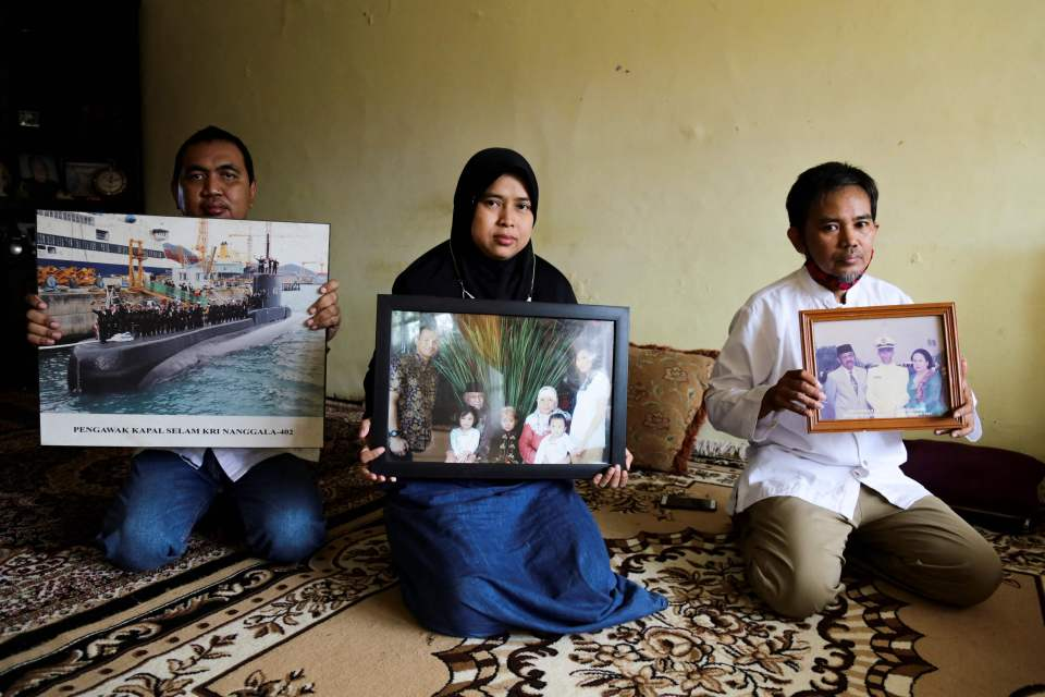 Relatives of those on board hold up pictures of them