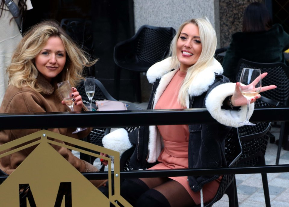 Women posed while enjoying a glass of champagne in an outdoor bar