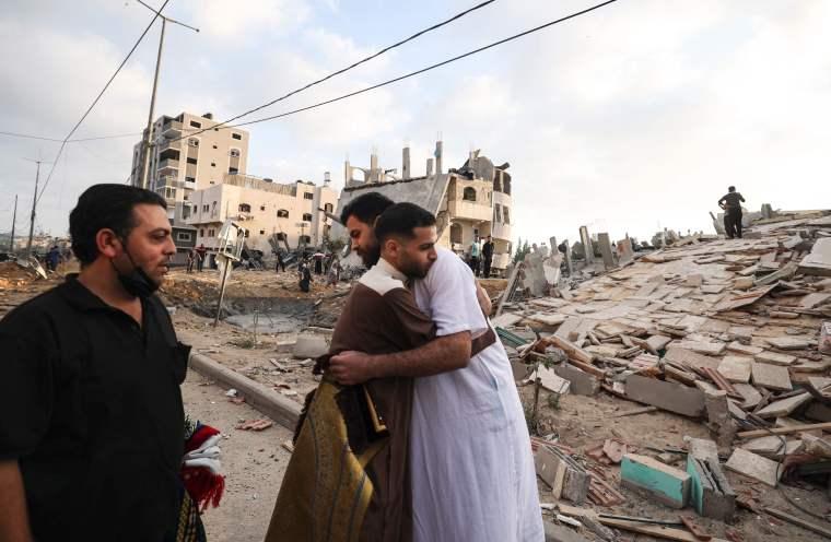 Hombres palestinos intercambian deseos festivos de Eid al-Fitr frente a un edificio destruido en Gaza