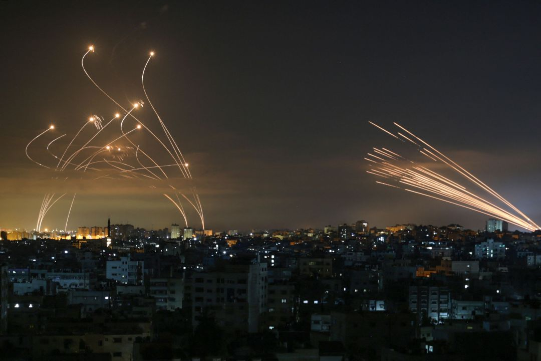 Missiles are seen in the night sky fired towards Israel (left) from Beit Lahia in the northern Gaza Strip - the Iron Dome interceptors are seen on the right