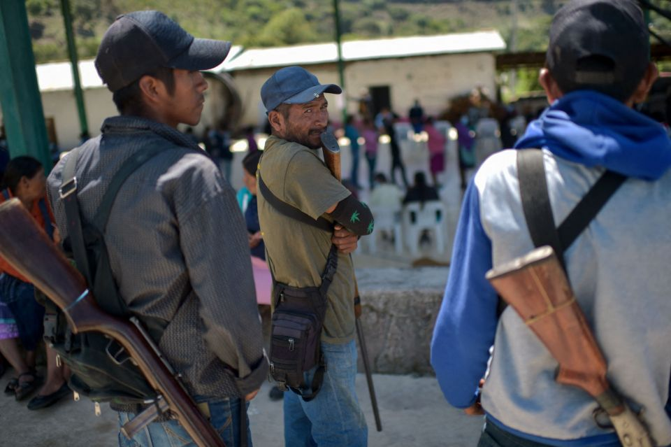 People queue to cast their votes while community policing stand guard at a polling station in Nahuat community of Ayahualtempa