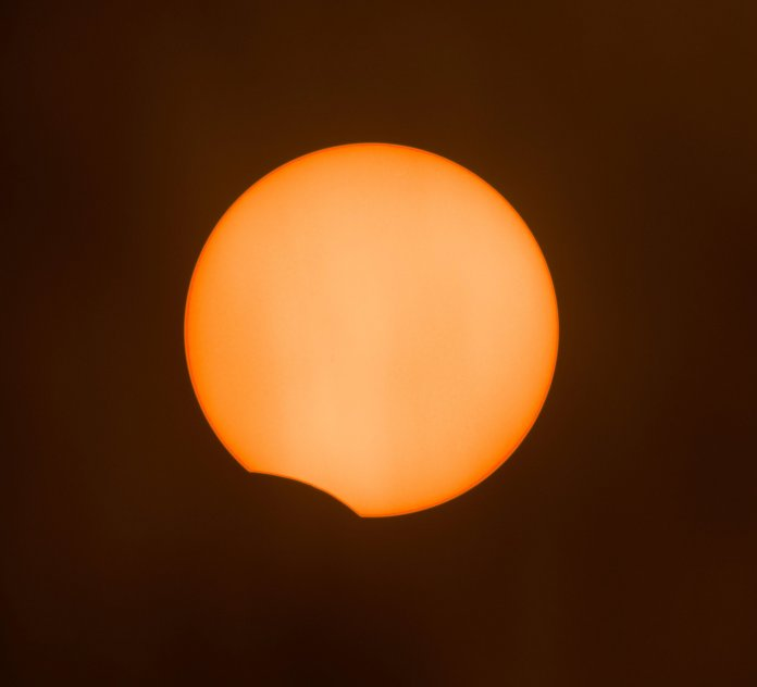 A partial solar eclipse is starting through a thick cloud over London