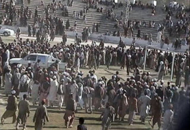 Crowds gather round to watch men being hanged by the Taliban at a football stadium in Afghanistan